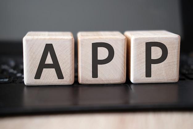 Słowo app na drewnianych kostkach na czarnej tablecie