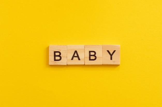 Słowo baby wykonane z drewnianych liter na żółtym tle.