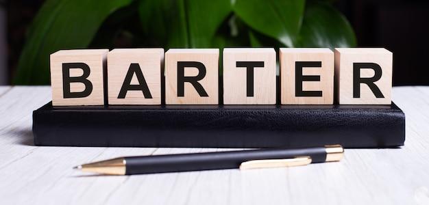 Słowo barter jest zapisane na drewnianych kostkach dziennika w pobliżu rączki.