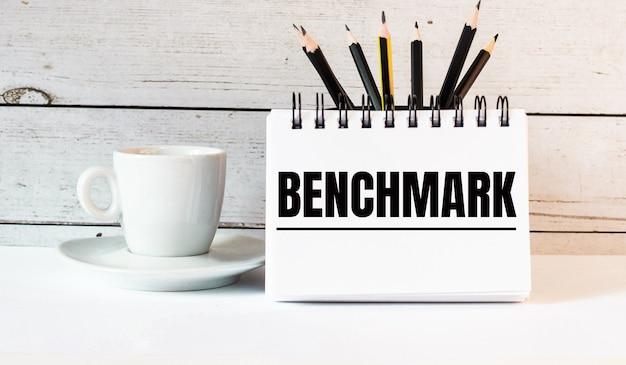Słowo benchmark jest zapisane w białym notesie obok białej filiżanki kawy na jasnej ścianie