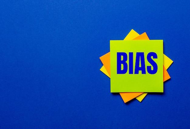 Słowo bias jest zapisane na jasnych naklejkach na niebieskiej ścianie