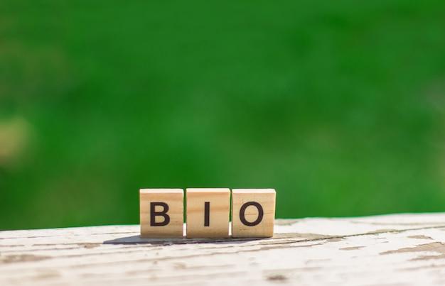 Słowo bio wiadomość znak drewnianych kostek na jasnym stole na tle zielonych liści w nieostrości