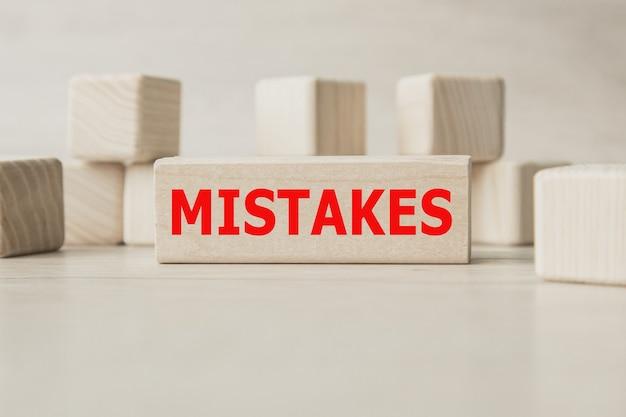 Słowo błędy jest zapisane na drewnianej konstrukcji z kostek