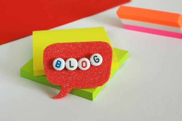 Słowo blog z plastikowych koralików w koralowym bąblu na stole z artykułami biurowymi