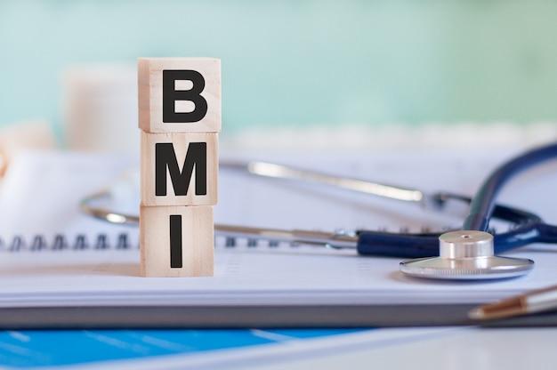 Słowo bmi jest zapisane na drewnianych kostkach obok stetoskopu na papierze. bmi - wskaźnik masy ciała. pojęcie medyczne.