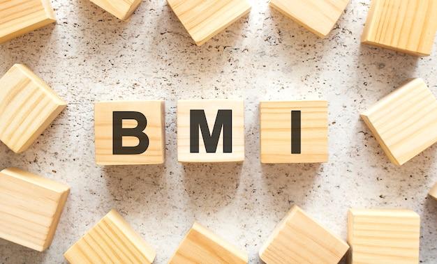 Słowo bmi to drewniane kostki z literami, widok z góry na jasnym tle. miejsce do pracy.