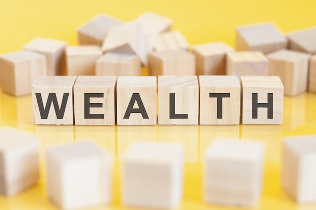 Słowo bogactwo jest zapisane na drewnianej konstrukcji z kostek. biznes, koncepcja finansowa.
