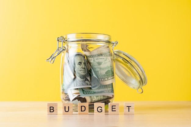 Słowo budżet i dolarowe rachunki w szklanym słoju na żółtym