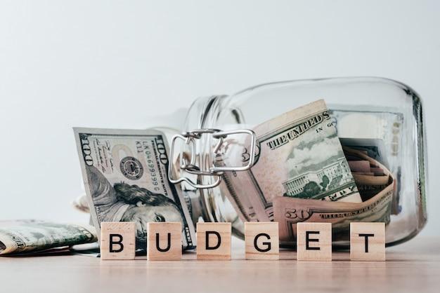 Słowo budżet i dolarowe rachunki w szklanym słoju