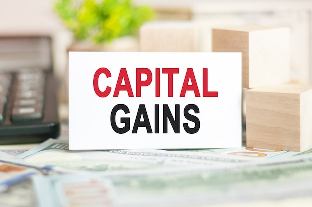Słowo capital gains jest zapisane na białej karcie papierowej obok drewnianej kostki, kalkulatora na ścianie z banknotami. koncepcja biznesowa i finansowa