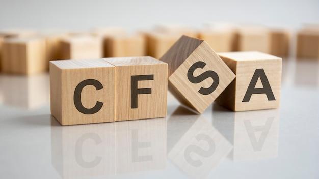 Słowo cfsa na drewnianych kostkach, szare tło