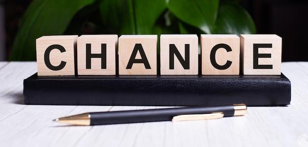 Słowo chance jest zapisane na drewnianych kostkach dziennika w pobliżu rączki