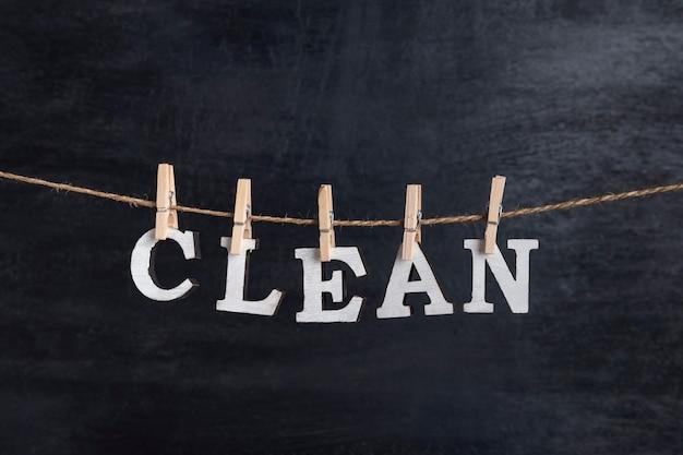 Słowo clean wisi na spinaczach do bielizny na czarnym tle.