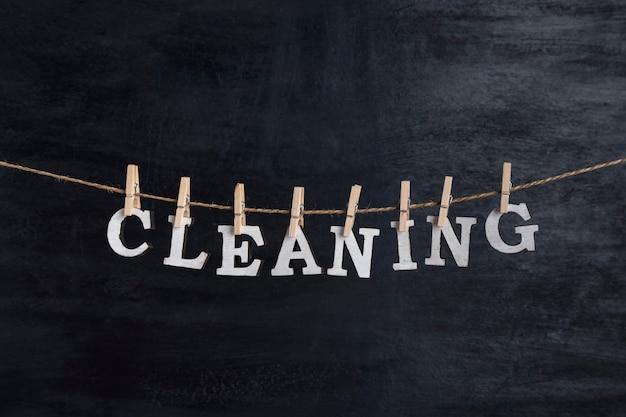 Słowo cleaning wisi na linie z spinaczy do bielizny na czarnym tle.