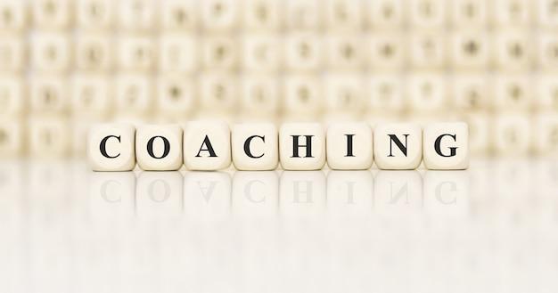 Słowo coaching napisane na drewnianym bloku. pomysł na biznes.