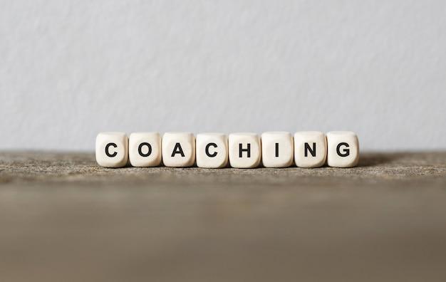 Słowo coaching wykonane z drewnianych klocków, zdjęcie stockowe