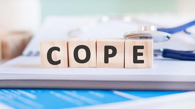 Słowo cope jest napisane na drewnianych kostkach w pobliżu stetoskopu na tle papieru. pojęcie medyczne.