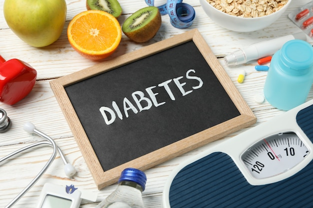 Słowo cukrzyca i akcesoria dla diabetyków na podłoże drewniane