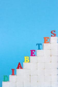 Słowo cukrzyca na drabinie rafinował cukier, błękitny tło.