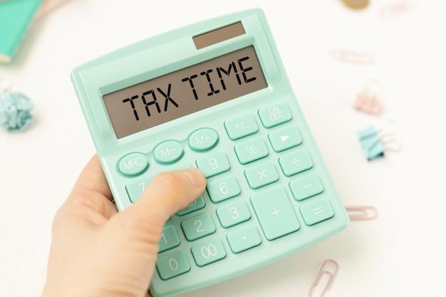 Słowo czas podatku na kalkulatorze. koncepcja biznesowa i podatkowa. czas na zapłacenie podatku w roku.