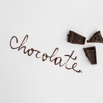 Słowo czekoladowe w pobliżu kawałków czekolady