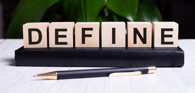 Słowo define jest zapisane na drewnianych kostkach leżących w dzienniku obok pióra.