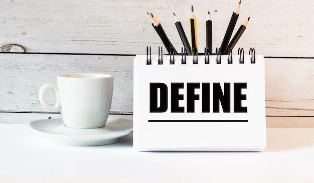 Słowo define jest zapisane w białym notatniku obok białej filiżanki kawy na jasnym tle