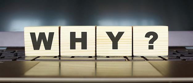 Słowo dlaczego. drewniane kostki z literami na białym tle na klawiaturze laptopa