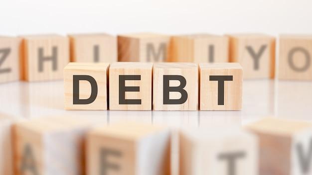 Słowo dług jest zapisane na drewnianej konstrukcji z kostek. koncepcja biznesowa i finansowa.