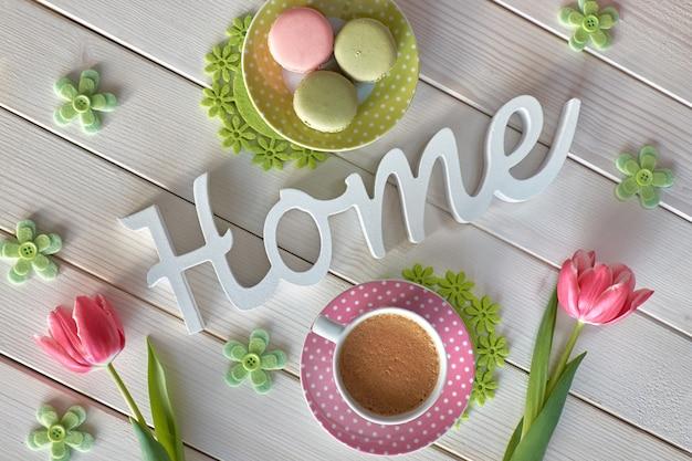 Słowo dom na białych drewnianych deskach z różowymi tulipanami, zielonymi kwiatami i zielonymi i różowymi macarons z kawą