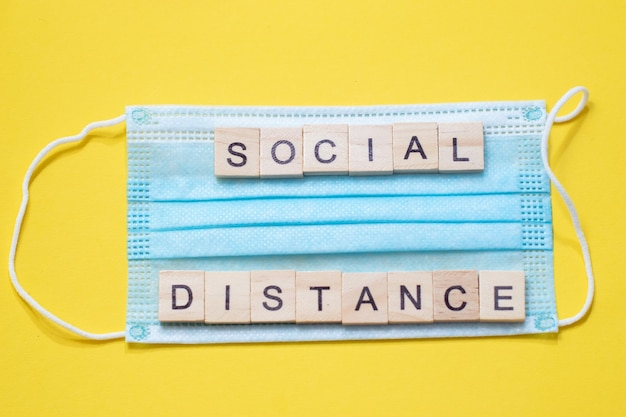 Słowo dystans społeczny wykonane z drewnianych liter na niebieskiej masce medycznej.