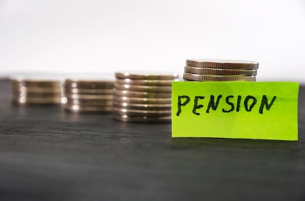 Słowo emerytura na naklejkach i stosach monet