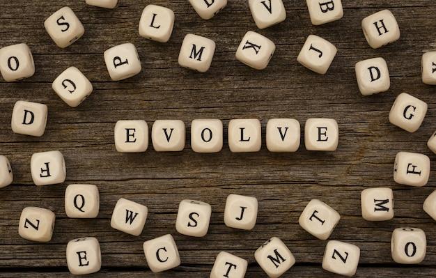 Słowo evolve napisane na drewnianym bloku