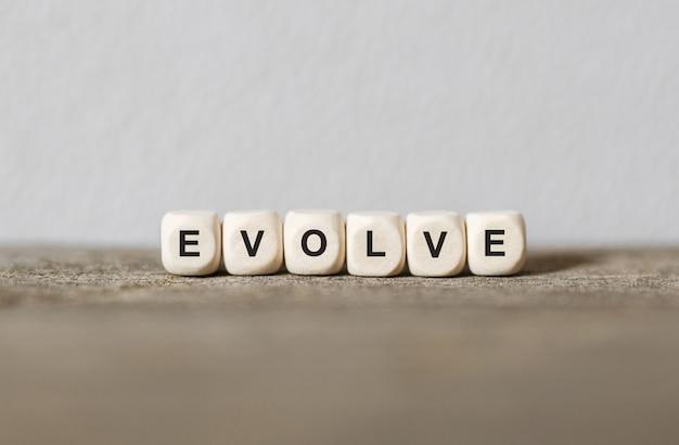 Słowo evolve wykonane z drewnianych klocków