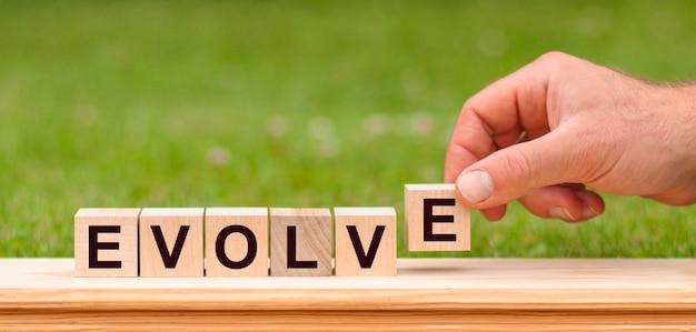 Słowo ewoluuje napisane drewnianymi klockami. mężczyzna ręka trzyma drewniany blok kostki z ewoluować - słowo biznesowe na tle zielony trawnik.