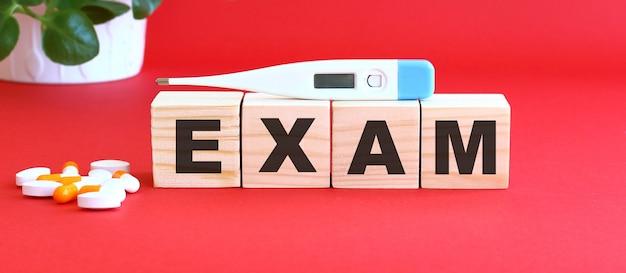 Słowo exam jest zrobione z drewnianych kostek na czerwono z lekarstwami.