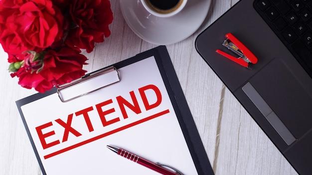 Słowo extend jest napisane na czerwono na białym notatniku obok laptopa, kawy, czerwonych róż i długopisu