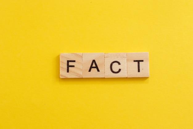 Słowo fakt wykonane z drewnianych liter na żółtym tle.