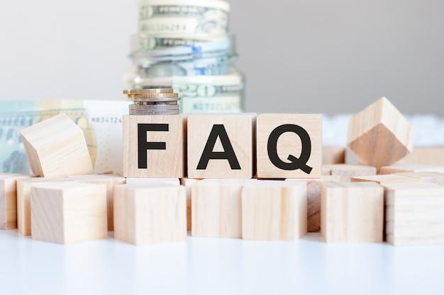 Słowo faq na drewnianych klockach i banku z pieniędzmi w tyle, koncepcja biznesowa