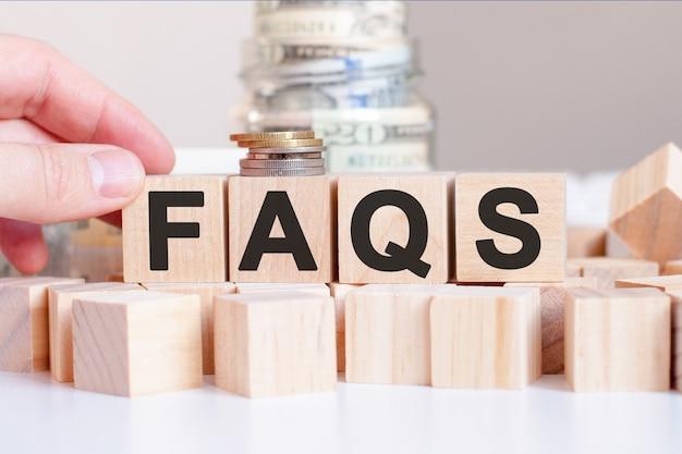 Słowo faqs na drewnianych klockach i banku z pieniędzmi w tyle, koncepcja biznesowa