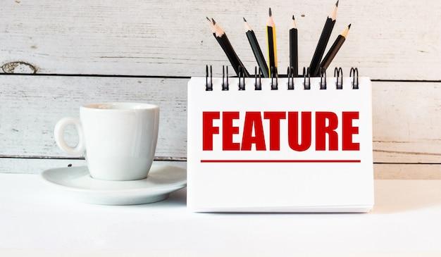 Słowo feature jest zapisane w białym notatniku obok białej filiżanki kawy na jasnej ścianie