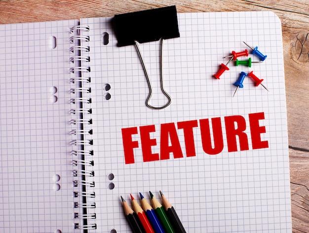 Słowo feature jest zapisane w zeszycie obok wielokolorowych ołówków i guzików na drewnianej powierzchni