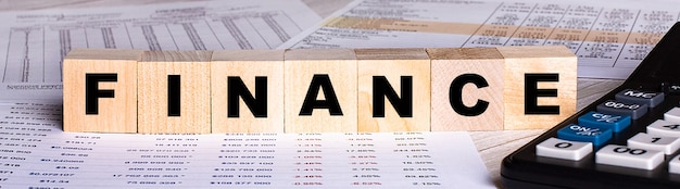 Słowo finance jest zapisane na drewnianych kostkach w pobliżu wykresów i kalkulatora.
