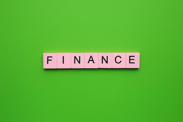 Słowo finansów na zielonym tle.