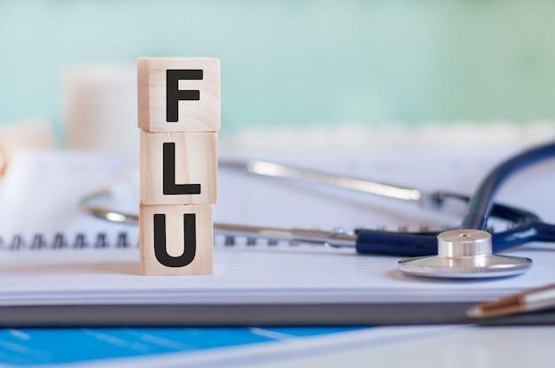 Słowo flu jest napisane na drewnianych kostkach w pobliżu stetoskopu na papierowym tle.