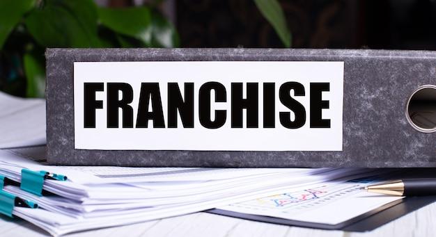 Słowo frachise jest zapisane w szarym folderze obok dokumentów. pomysł na biznes.
