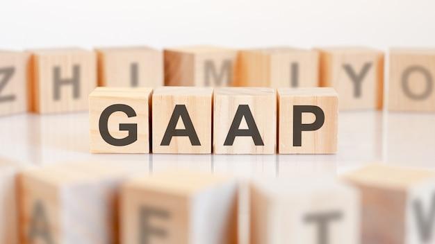 Słowo gaap z drewnianych klocków z literami, właściciel lub robienie koncepcji biznesowej, losowe litery wokół, białe tło. gaap – skrót od ogólnie przyjętych zasad rachunkowości