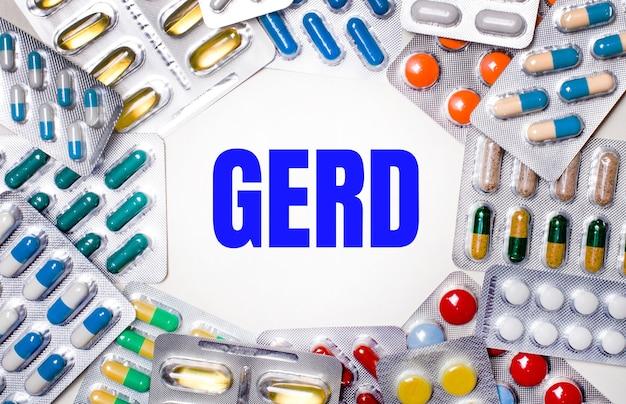 Słowo gerd jest napisane na jasnym tle, otoczone wielokolorowymi opakowaniami z tabletkami. koncepcja medyczna