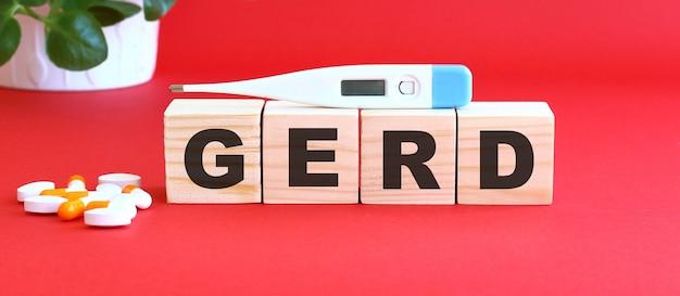 Słowo gerd składa się z drewnianych kostek na czerwonym tle z lekarstwami.