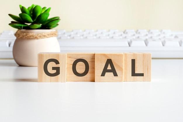 Słowo goal wykonane z drewnianych klocków. koncepcje widoku z przodu, zielona roślina w wazonie z kwiatami i biała klawiatura na tle